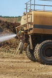 Mining Photo Stock Library - close up of water cart sprying watewr on haul road for dust suppression. ( Weight: 1  New Image: NO)