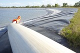 Mining Photo Stock Library - tailings dam with rubber lining.  pipe entering from foreground and orange floats in water. ( Weight: 1  New Image: NO)