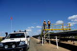 Mining Photo Stock Library - two mine workers in full PPE standing on pedestrian overpass with overland covered coal conveyor below. conveyor stretches into background and light vehicle on access road adjacent. ( Weight: 1  New Image: NO)