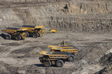 Mining Photo Stock Library - 4 four haul trucks parked at go line in open cut coal mine.  worker in full PPE gives scale of machines.   ( Weight: 1  New Image: NO)