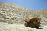 Mining Photo Stock Library - wide shot at ground level of loaded haul truck leaving the deep open cut pit floor.  excavator and dozer in background at base of high wall.  blue sky and high walls above.  gold mine. ( Weight: 1  New Image: NO)