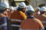 Mining Photo Stock Library - mine worker in full PPE at site meeting with lots of workers in background.  very generic shot with no faces and those in the background out of focus. ( Weight: 1  New Image: NO)
