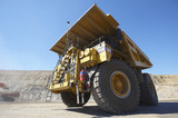 Mining Photo Stock Library - dramatic photo of a haul truck in open cut coal mine.  shot from ground level almost under front wheel.  blue sky behind. ( Weight: 1  New Image: NO)