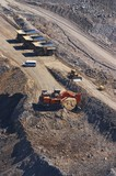 Mining Photo Stock Library - large excavator diggin overburden in open cut coal mine.  haul trucks parked up at go line in background.  aerial vertical image.  light vehicle mini bus transporting truck drivers in middle ground. ( Weight: 1  New Image: NO)