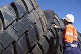 Mining Photo Stock Library - mine worker in full PPE inspecting truck tyre stockpile. ( Weight: 1  New Image: NO)