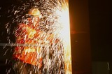 Mining Photo Stock Library - mine construction worker in full PPE using an angle grinder whilst standing in cage confine of EWP - elevated work platform.  shot at night and lots of sparks. ( Weight: 1  New Image: NO)
