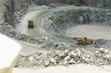 Mining Photo Stock Library - loader and haul truck rotation in quarry. shot from up high behind a workers helmet looking down on the action. ( Weight: 1  New Image: NO)