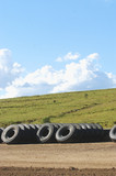 Mining Photo Stock Library - truck tyre stock pile on mine site with green revegetation in the background.  vertical image. ( Weight: 1  New Image: NO)