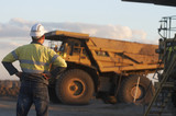 Mining Photo Stock Library - worker in full PPE with hands on hips observing haul trucks at the go line.  shot in the late afternoon light. ( Weight: 1  New Image: NO)