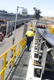 Mining Photo Stock Library - mine supervisor in full PPE on walkway next to coal conveyor at a coal terminal. shot from behind, cannot see the persons face. ( Weight: 1  New Image: NO)