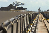 Mining Photo Stock Library - dramatic shot looking along conveyor to reclaimers and stockpiles at a coal terminal.  selective focus with foreground in focus. ( Weight: 1  New Image: NO)