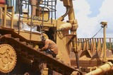 Mining Photo Stock Library - mine worker servicing a large dozer at a workshop at a mining site. ( Weight: 1  New Image: NO)