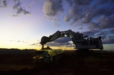 Mining Photo Stock Library - dusk photo of excavator loading overburden into haul truck in open cuit mine site. machines with lights on and great colour in the sky.  generic production image. ( Weight: 1  New Image: NO)