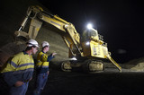 Mining Photo Stock Library - shot at night, two 2 mine site workers in full PPE down in the open cut coal mine pit discussing next move with large excavator with lights on in the background. ( Weight: 1  New Image: NO)
