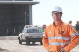 Mining Photo Stock Library - mine site worker in full PPE looking straight at the camera in front of workshop. light vehicle driving in background.  space for copy on left hand side. ( Weight: 1  New Image: NO)