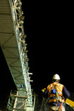 Mining Photo Stock Library - rigger worker in full PPE including a harness working under a bridge at night.  crane and scaffolding in the background.  shot from behind. ( Weight: 1  New Image: NO)