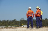 Mining Photo Stock Library - three mine site workers in full PPE in discussion.  workers out of focus.  vertical shot. ( Weight: 1  New Image: NO)
