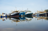 Mining Photo Stock Library - fishing trawler boats moored in a clean water harbour.  photo taken at water level with blue sky behind. ( Weight: 1  New Image: NO)