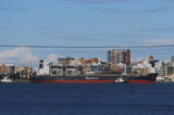 Mining Photo Stock Library - large ship being shepherded by a tug into port.  residential and town behind. ( Weight: 1  New Image: NO)