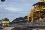 Mining Photo Stock Library - coal train unloading at a stockpile with shiploader in foreground.  blue sky behind. ( Weight: 1  New Image: NO)