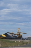 Mining Photo Stock Library - photo of large shiploader and reclaimer working on coal stockpiles. light vehicle sealed road in foreground.  vertical photo. ( Weight: 1  New Image: NO)